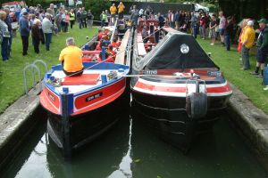Working boats carrying the band leaving Langley Bridge lock